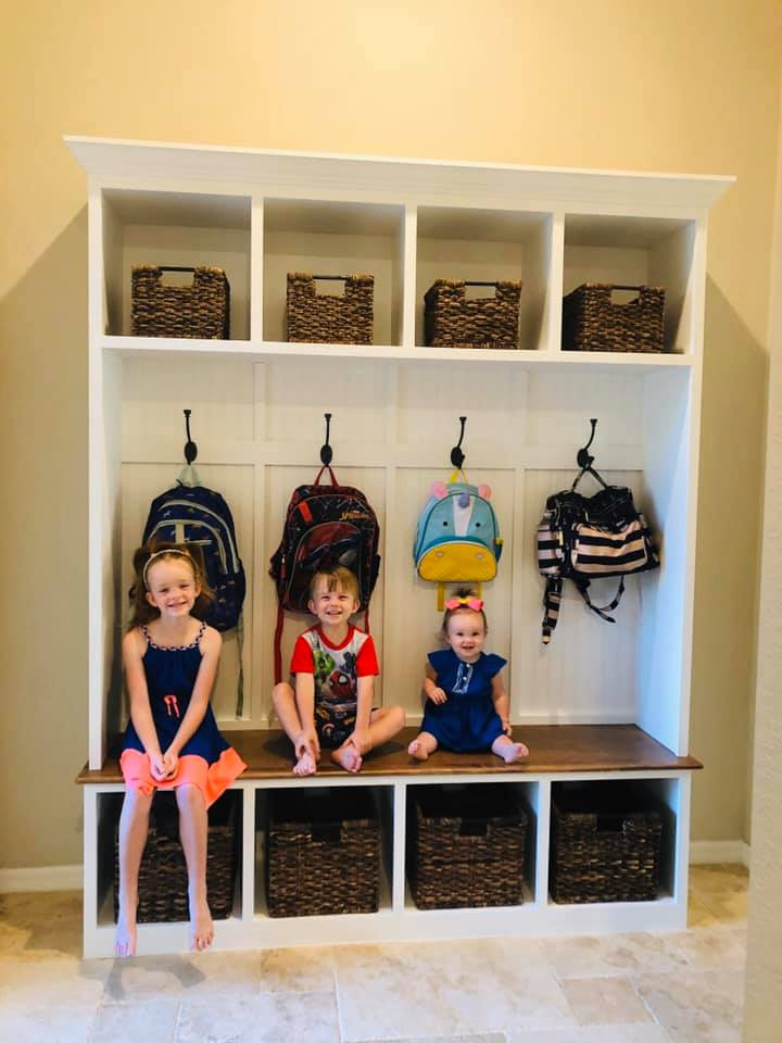 Kids Sitting On Decorated Mudroom Bench